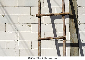 Wood ladder leaning on white brick wall