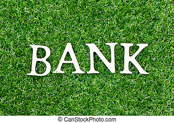 Wood letter in word bank on green grass background