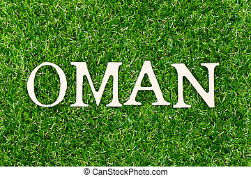 Wood letter in word oman on green grass background