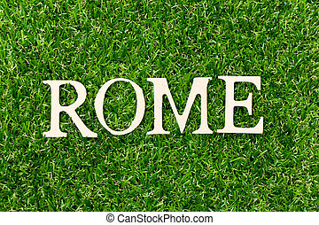 Wood letter in word Rome on green grass background