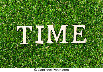 Wood letter in word time on green grass background