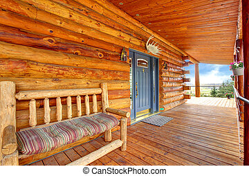 Wood log cabinet porch with entrance and bench.