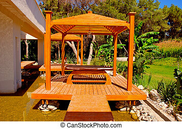 wood pavilion in tropical garden on summer resort -...