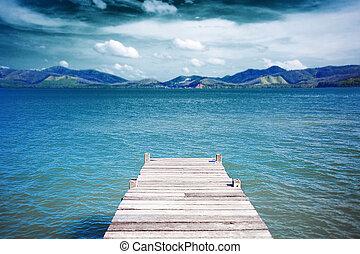 wood pier on the sea under blue sky