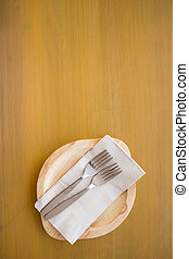wood plate with fork on wooden table.