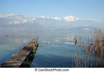 Wood pontoon, water, reeds bed and snowed mountains on Annecy lake, France