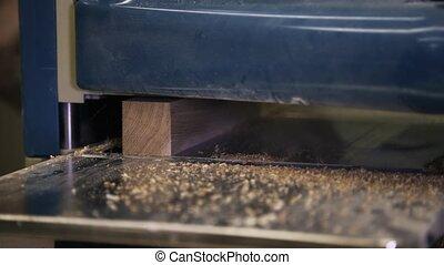 Wood processing by using an industrial tool. Sanding a bar.. Sanding a bar.