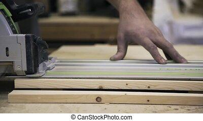 Wood processing using a Circular Saw. Sawing a bar.