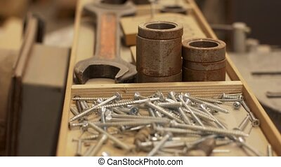 wood screws and tools in box at workshop - production,...