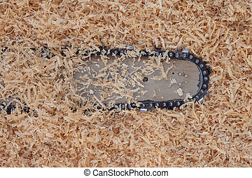 Background with softwood shavings and chainsaw blade with sharp teeth.