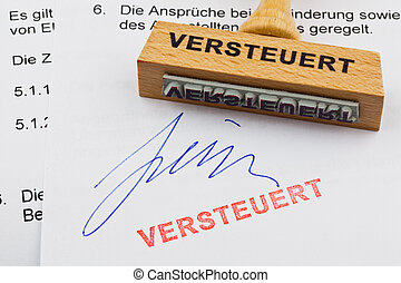 wood stamp on the document: tax - a stamp made of wood lying...