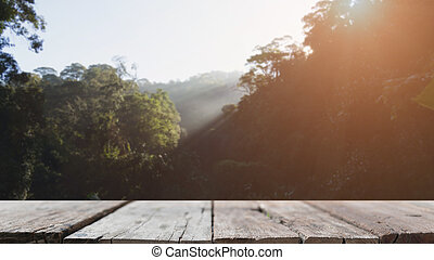 wood table and blur image of green tree in forest with sun rays for background usage