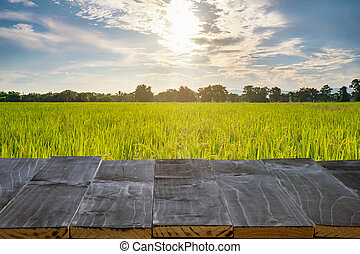 wood table for product montage and display with rice field sunlight,