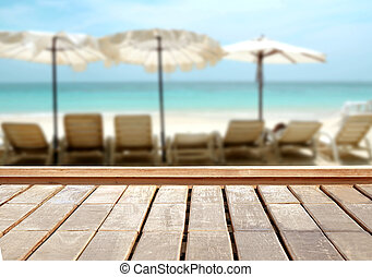 Wood table top on blurred blue sea and white sand beach background