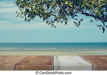 Wood table top on blurred blue sea