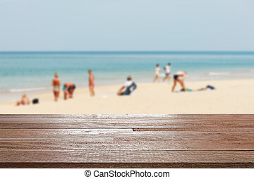 Wood table top on blurred blue sea and white sand beach with some people