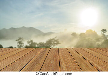 Wood table top on blurred mountain at morning sunrise background for presentation product.