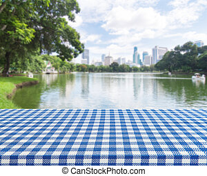 Wood table with blue table cloth on blur park background for display montage your products