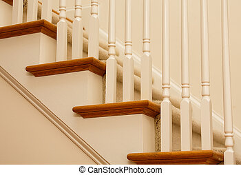 Details of an interior staircase with stained hardwood, painted pickets and carpet