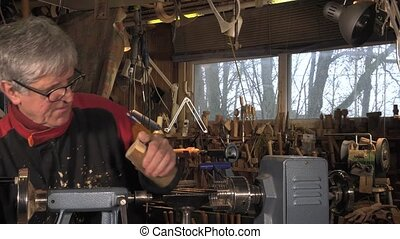 hands shape the rotating block of wood