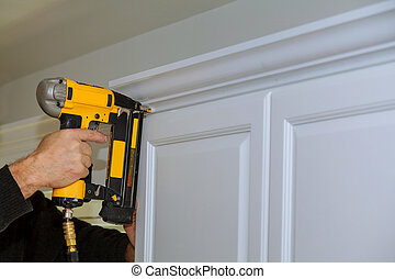 Wood working using brad nail gun to Crown Moulding on white...