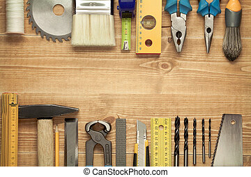 Working tools on a wooden boards background. Including saw, ruler, drill, nails, pliers, hammer, brush, thread, chisel and other.