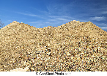 Enormous pile of woodchips from local deforestation. Beautiful blue sky in the background.