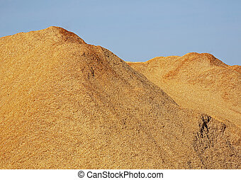 Pile of wood chips, sawdust against a blue sky.