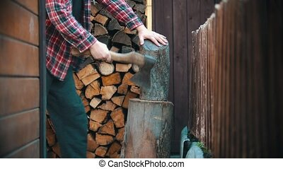 Woodcutter about to chop big log with an ax in woodpile. Mid shot