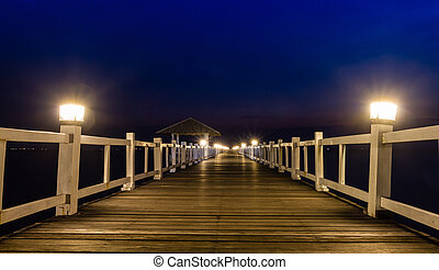 Wooded bridge in the port at night
