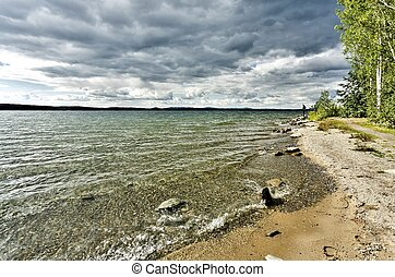 wooded shore on the background of the lake and cloudy sky