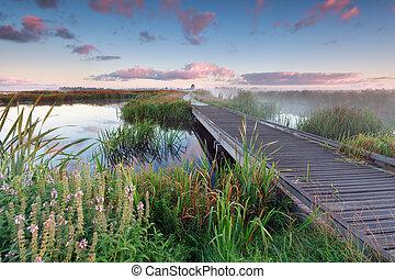 woodem bike path on lake water at sunrise