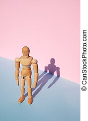 Woodem man figure on pink and blue background