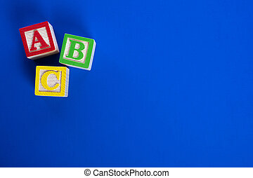 Wooden ABC blocks on blue background