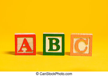 Wooden ABC blocks on yellow background
