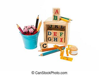 Wooden alphabet block with pencils