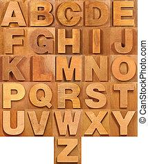 Wooden alphabet font on brown wooden background