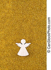 Wooden angel on golden glitter background