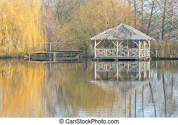 Wooden arbour in autumn by a lake with reflections