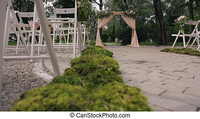 Wooden arch with curtains, flowers for ceremony on wedding day