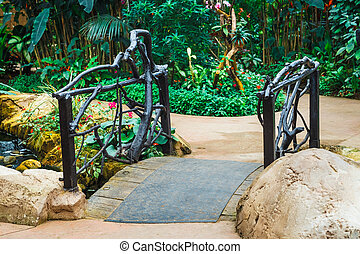 wooden arched bridge in the green garden