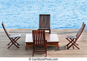 Wooden area with chairs and table on water