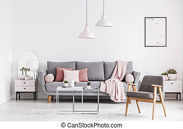 Wooden armchair and poster in white living room interior with pink blanket on grey couch. Real photo