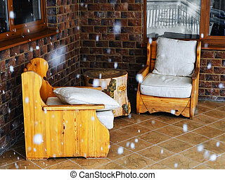 Wooden armchairs with soft seats and a table in the form of a log by the window on a covered terrace during a snowfall