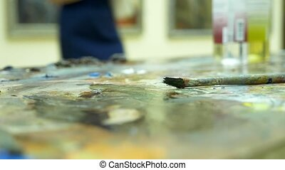 Wooden art palette with oil paints. Mixing colors together,...