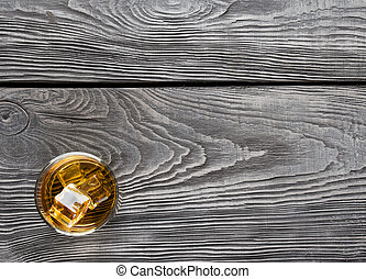 Wooden background with a glass of whiskey