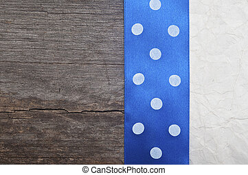 wooden background with blue polka-dot ribbon on crumpled paper