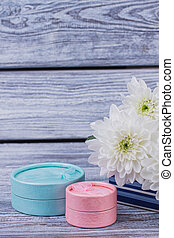 Wooden background with flowers and gift boxes.