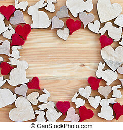 Wooden background with hearts and easter bunnies