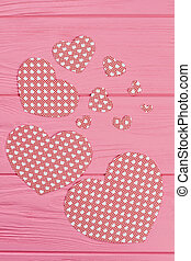 Wooden background with paper hearts, top view.